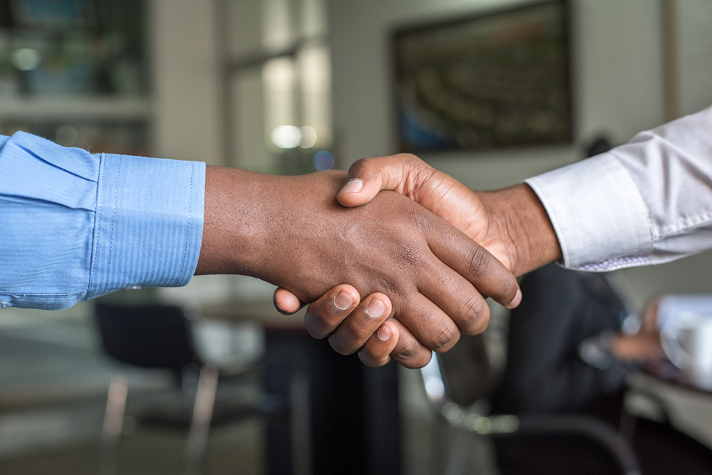 Two people giving each other a handshake.