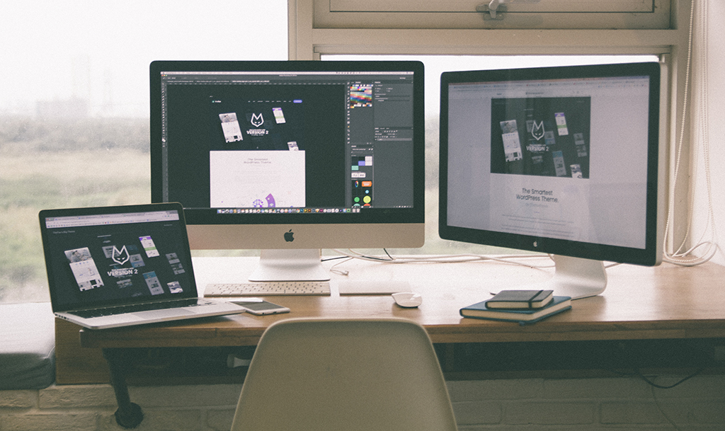 Multiple monitors displaying the beginning stages of website development.