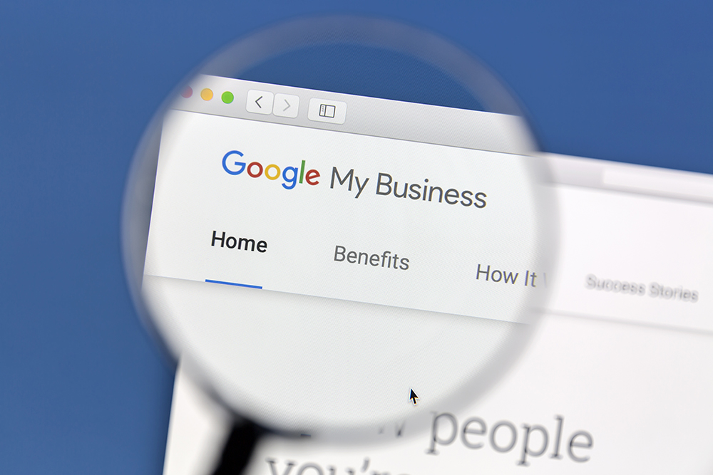 Google Business Listing logo under a magnifying glass against a blue backgorund.