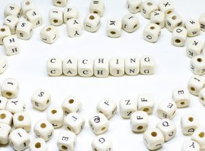 """White beaded letters spelling out """"Caching."""""""