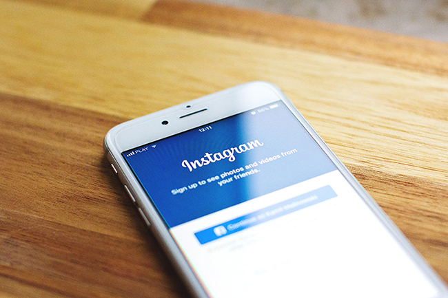 Cell phone opened up to the Instagram followers app, sitting on a wooden table.