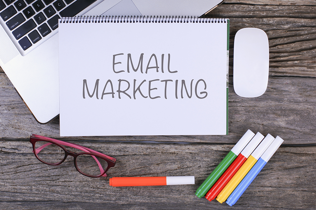 Email Marketing written on a piece of paper with colored markers, glasses, and a laptop surrounded the page.