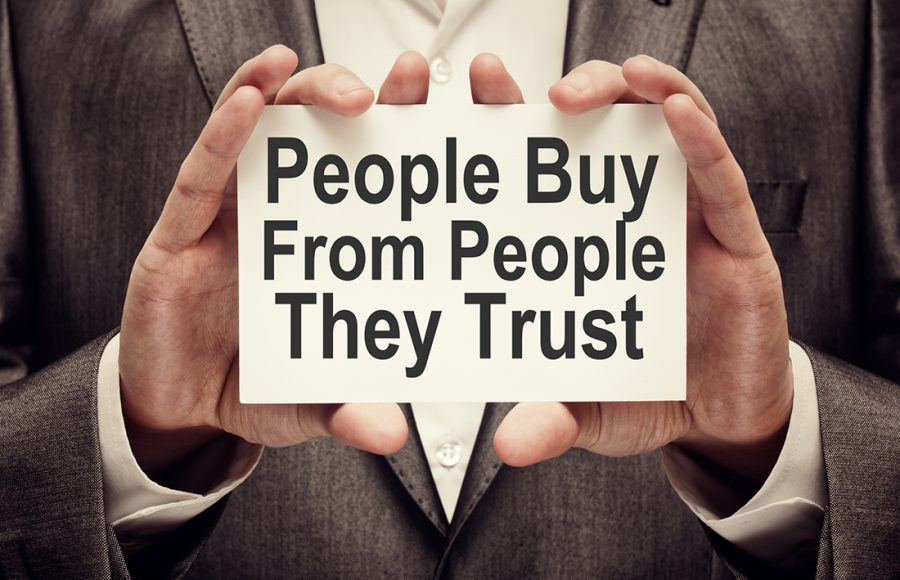 """White card with, """"people buy from people they trust"""" written on it for proper brand management.."""